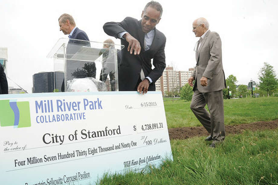 Milton Puryear, executive director for Mill River Collaborative, unveils the $4.7 million dollar check Monday at the groundbreaking held at the park.