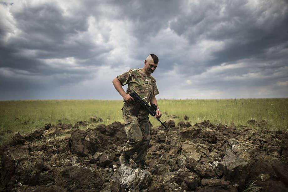 A Ukrainian serviceman investigates a crater left by a Grad rocket in the village of Toshkivka, Luhansk region, eastern Ukraine, Monday, June 15, 2015. (AP Photo/Evgeniy Maloletka)
