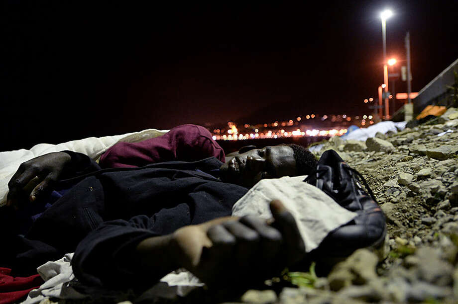 A migrant sleeps on the ground in Ventimiglia, at the border between Italy and France, early Monday, June 15, 2015. A standoff between nearly 200 migrants and the French border police has entered its fourth day with would-be refugees refusing to leave Italy's Mediterranean border with France in hopes of continuing their journeys north. (AP Photo/Massimo Pinca)