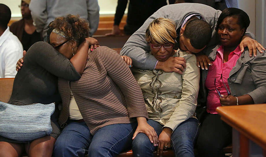 The family and supporters of Dushawn Taylor-Gennis, including his mother Genneane Gennis, seated second from right, react at the end of the session in Dorchester Municipal Court in Boston, Monday, June 15, 2015. Taylor-Gennis and Raeshawn Moody have been charged with gunning down Jonathan Dos Santos out riding his bike and have been held without bail. (Pat Greenhouse/The Boston Globe via AP, Pool)