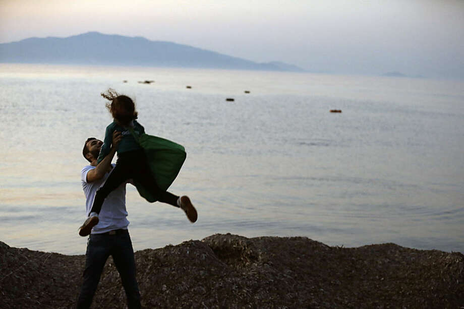 A Syrian migrant holds up her daughter as lifejackets float on the water after their arrival from Turkish coasts at a beach in Mytilene, on the northeastern Greek island of Lesvos, early Tuesday, June 16, 2015. Lesvos has been bearing the brunt of a huge influx of migrants from the Middle East, Asia and Africa crossing from the Turkish coast to nearby Greek islands. More than 50,000 migrants have arrived in Greece already this year, compared to 6,500 in the first five months of last year. (AP Photo/Thanassis Stavrakis)