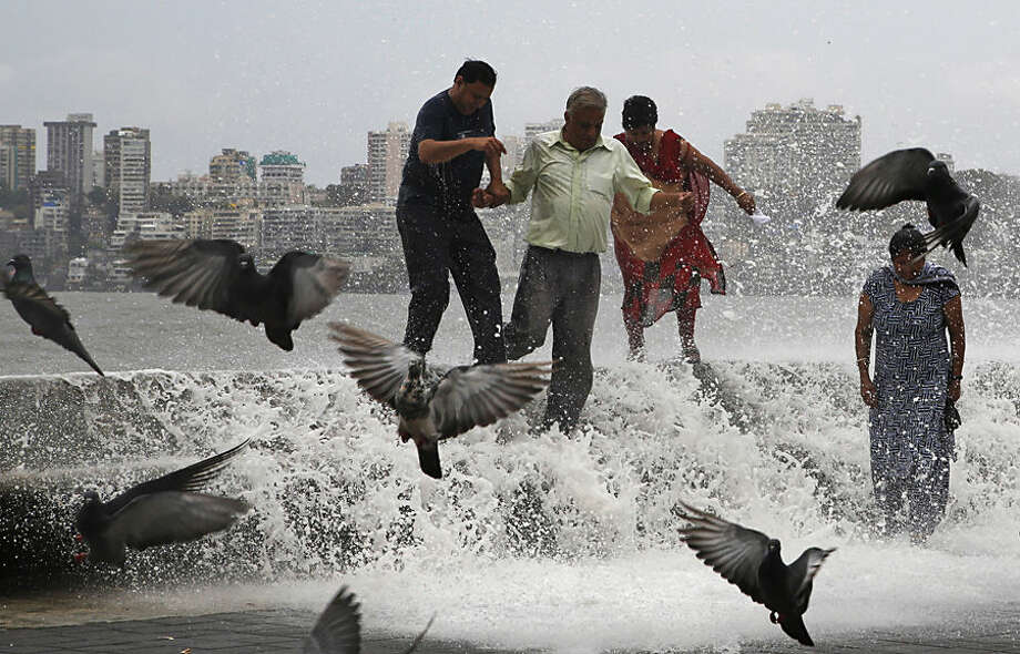 Indians try to walk away as huge tidal waves hit the Arabian Sea shore marking the arrival of monsoon season in Mumbai, India, Tuesday, June 16, 2015. The annual monsoon rains which usually hit India from June to September are crucial for farmers whose crops feed hundreds of millions of people. (AP Photo/Rajanish Kakade)