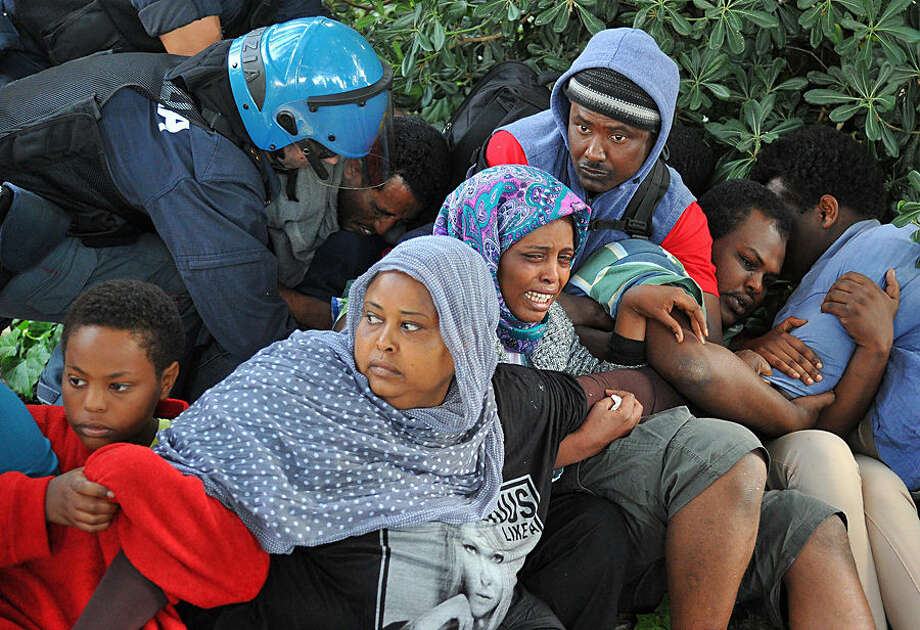 Italian Police remove migrants in Ventimiglia, at the Italian-French border Tuesday, June 16, 2015. Police at Italy's Mediterranean border with France have forcibly removed some of the African migrants who have been camping out for days in hopes of continuing their journeys farther north. The migrants, mostly from Sudan and Eritrea, have been camped out for five days after French border police refused to let them cross. (Luca Zennaro/ANSA via AP)