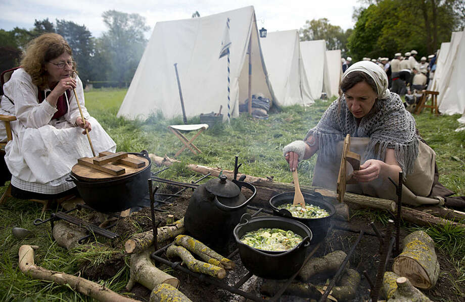In this May 9, 2015, photo, two women, dressed in Napoleonic era dress, cook a lunchtime soup for re-enactors of the 7th Battalion of the Line at a Napoleonic era living history camp in Elewijt, Belgium. The Belgian-Dutch living history group is coordinating their group for participation in the 200th anniversary of the Battle of Waterloo which will take place in June 2015. (AP Photo/Virginia Mayo)