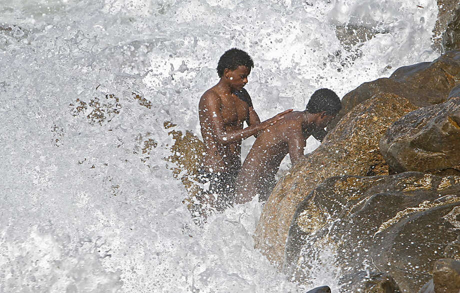 Migrants wash in the Mediterranean sea at the Franco-Italian border near Menton, southeastern France, Monday, June 15, 2015. Some 150 migrants, principally from Eritrea and Sudan, attempted to cross the border from Italy and have been blocked by French and Italian authorities. (AP Photo/Lionel Cironneau)