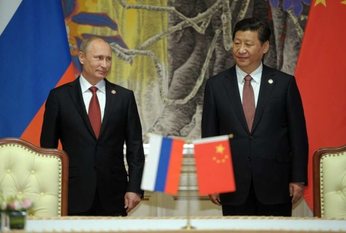FILE - In this May 21, 2014 file photo, Russia's President Vladimir Putin, and China's President Xi Jinping, right, smile during a signing ceremony on a natural gas deal between their two countries, in Shanghai, China. Angry with the West's response over Ukraine, Russia is moving rapidly to bolster ties with North Korea in a diplomatic nose-thumbing that could complicate the U.S.-led effort to squeeze Pyongyang into giving up its nuclear weapons program. Russia's proactive strategy in Asia- which also involves cozying up to China and had been dubbed