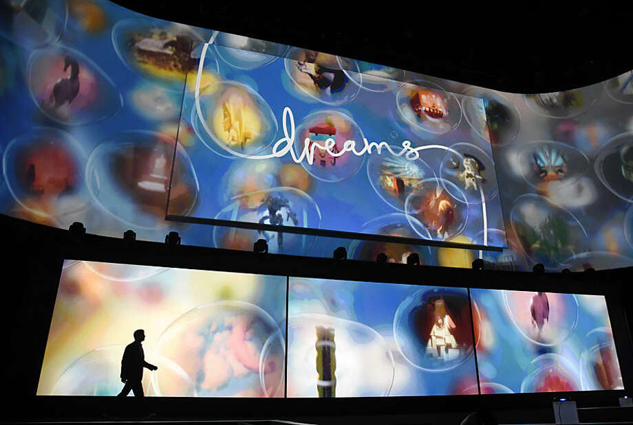 "Asad Qizilbash, head of software marketing for Sony Computer Entertainment America, walks out onstage as graphics from the video game ""Dreams"" are displayed during the Sony Playstation at E3 2015 news conference at the Los Angeles Sports Arena on Monday, June 15, 2015, in Los Angeles. (Photo by Chris Pizzello/Invision/AP)"