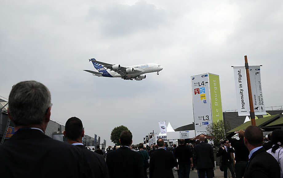 Visitors watch an Airbus A380 during a demonstration flight of the Paris Air Show, at Le Bourget airport, north of Paris, Monday, June 15, 2015. Some 300,000 aviation professionals and spectators are expected at this week's Paris Air Show, coming from around the world to make business deals and see dramatic displays of aeronautic prowess and the latest air and space technology. (AP Photo/Christophe Ena)