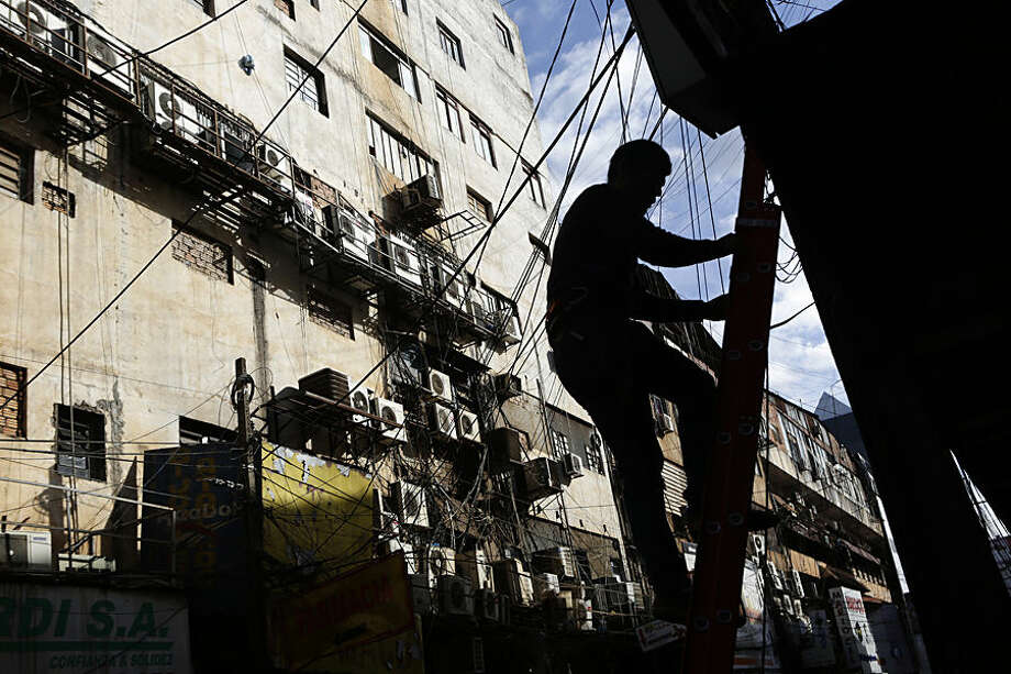In this May 13, 2015 photo, an electricity worker climbs down a ladder in Ciudad del Este, Paraguay. The city of 350,000 is a hub for immigrants from all corners, where the city streets buzz with vendors negotiating in Chinese, Arabic, Spanish and indigenous Guarani. (AP Photo/Jorge Saenz)