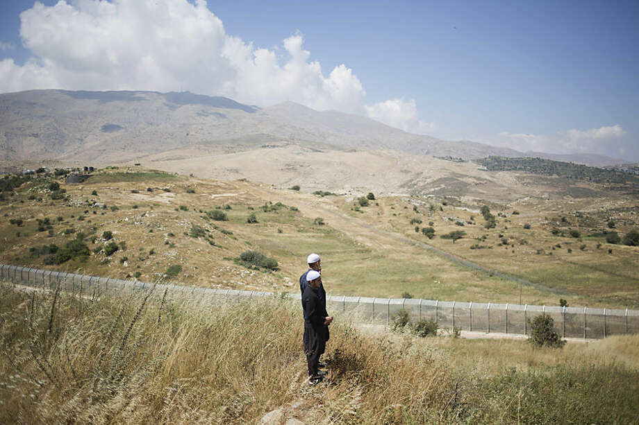 Members of Israel's Druze minority look at the the fighting between between forces loyal to Syrian President Bashar Assad and rebels in the Druze village of Khader in Syria, from the Israeli controlled Golan Heights, Tuesday, June 16, 2015. As many as 20 members of the Druze minority sect were killed last week, the deadliest violence against the Druze since Syria's conflict started in March 2011, sparking fears of a massacre against the sect. (AP Photo/Ariel Schalit)
