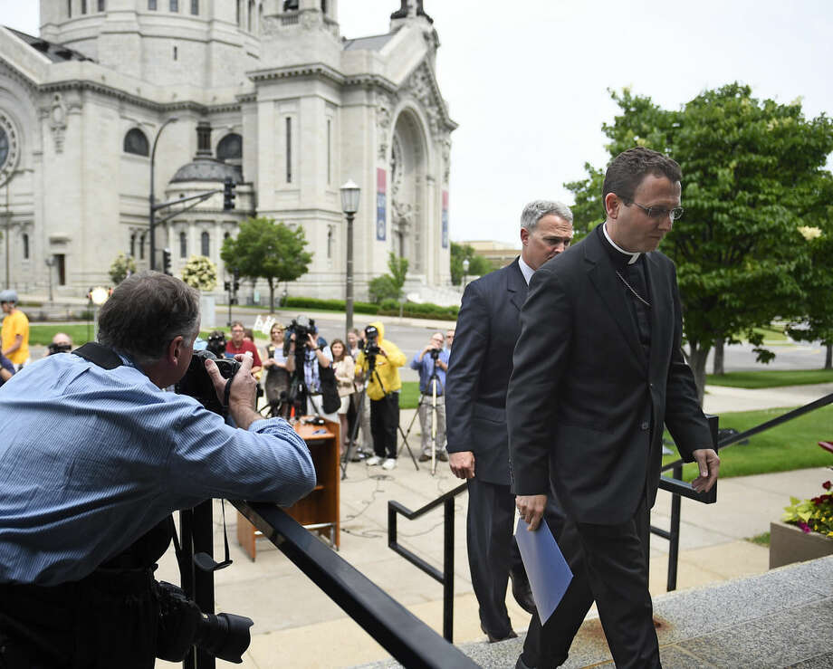 Auxiliary Bishop Andrew Cozzens, right, and Tom Halden, director of communications for the Archdiocese of Saint Paul & Minneapolis, walk back to the chancery after announcing the resignations of Archbishop John Nienstedt and Auxiliary Bishop Lee Anthony Piche during a news conference at the Archdiocese of Saint Paul & Minneapolis Chancery in St. Paul Minn., Monday, June 15, 2015. In the last two years, Nienstedt was besieged by a clergy sex-abuse scandal that included numerous lawsuits from victims and led to bankruptcy. Then earlier this month, the archdiocese was criminally charged with failing to protect children. (AP Photo/Craig Lassig)