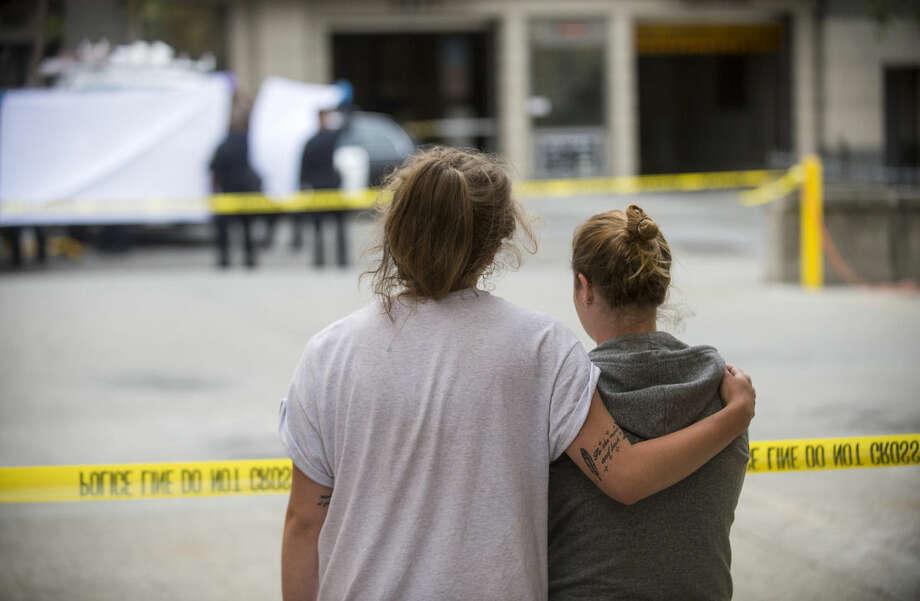 Two women embrace while watching sheriff's deputies move the body of a person who died when a fourth floor balcony collapsed in Berkeley, Calif. on Tuesday, June 16, 2015. The two said they knew the victims of the collapse. Berkeley police say several people are dead and others injured after a balcony fell shortly before 1 a.m., near the University of California, Berkeley. (AP Photo/Noah Berger)