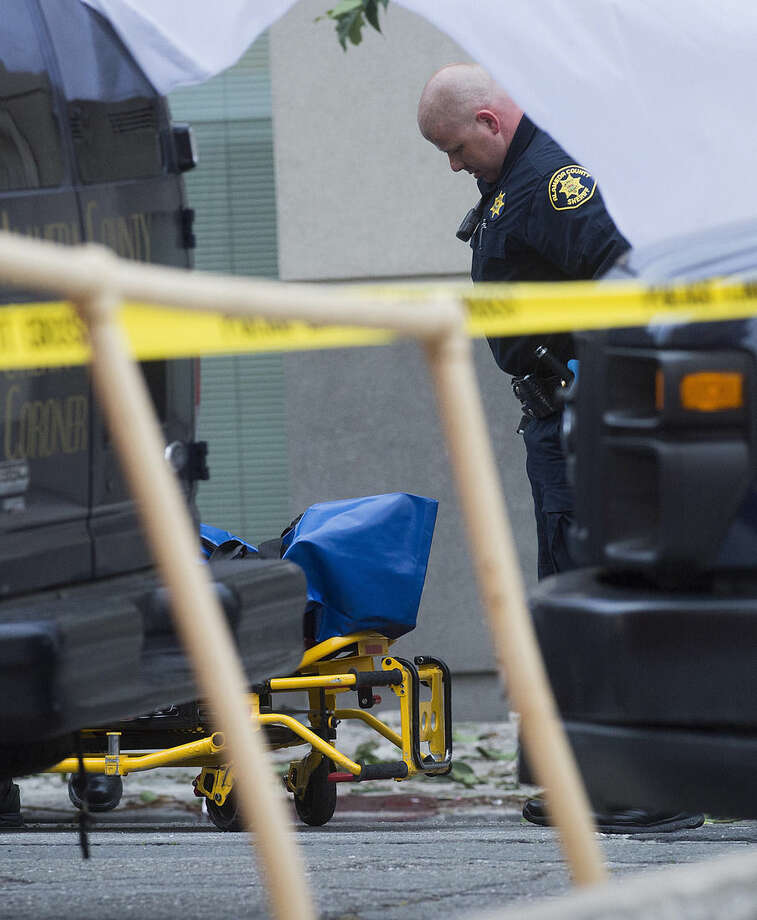 A sheriff's deputy prepares to move the body of a person who died when a fourth floor balcony collapsed in Berkeley, Calif. on Tuesday, June 16, 2015. Berkeley police say several people have dead and others were injured after the Library Gardens apartment balcony collapsed shortly before 1 a.m. near the University of California, Berkeley. (AP Photo/Noah Berger)