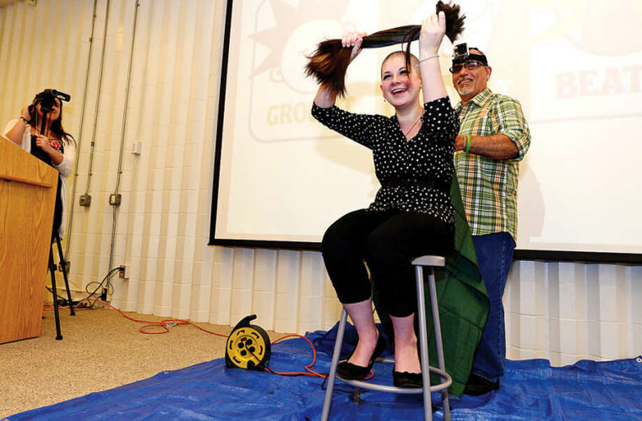 Hour photo / Erik Trautmann Jennifer Pohl, a Norwalk High School sophomore, has her head shaved in the school's Public Forum Room Friday monring to benefit cancer research. Pohl has raised $660 dollars so far for the St. Baldrick's Organization to help fight cancer.