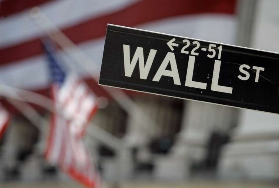 FILE - In this May 11, 2007, file photo, a Wall Street sign is mounted near the flag-draped facade of the New York Stock Exchange. Corporate earnings season is off to a positive start, helping lift the stock market Wednesday, July 9, 2014, after two days of declines. (AP Photo/Richard Drew, File)