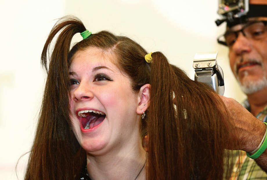Hour photo / Erik Trautmann Jennifer Pohl, a Norwalk High School sophomore, has her head shaved in the school's Public Forum Room Friday morning to benefit cancer research. Pohl has raised $660 dollars so far for the St. Baldrick's Organization to help fight cancer.