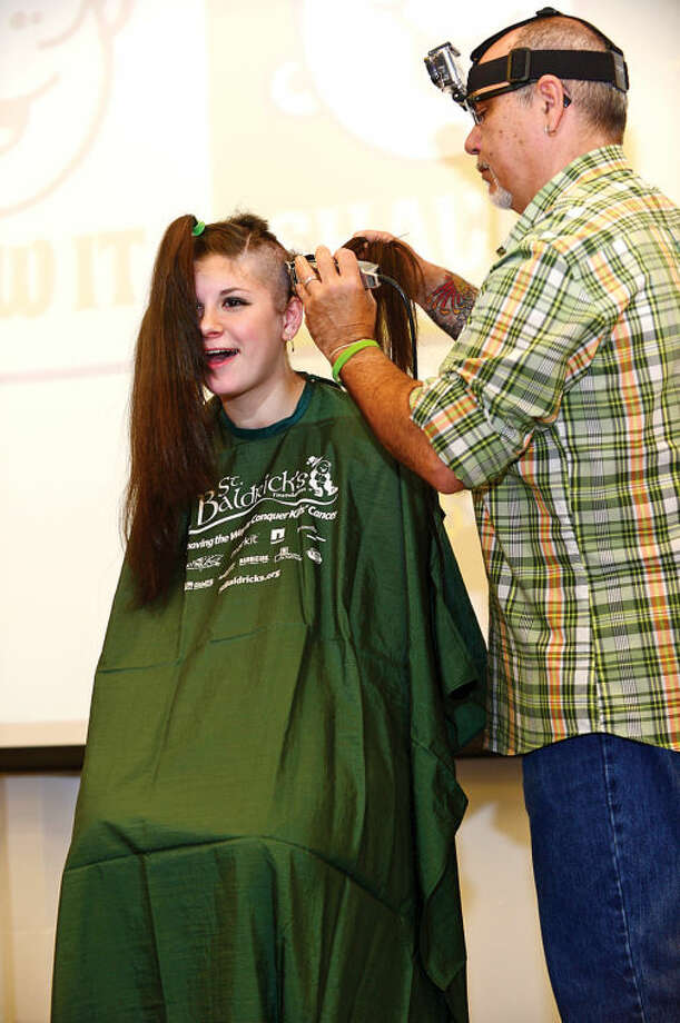 Hour photo / Erik Trautmann Jennifer Pohl, a Norwalk High School sophomore, has her head shaved by Mane Street Salon's Victor LaCanfora in the school's Public Forum Room Friday morning to benefit cancer research. Pohl has raised $660 dollars so far for the St. Baldrick's Organization to help fight cancer.