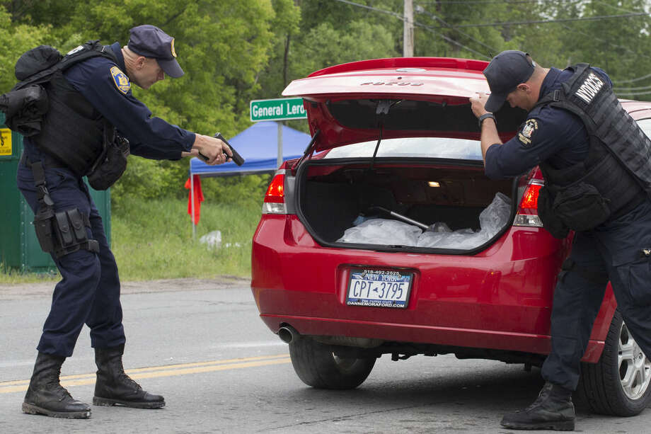 An officer with the New York State Department of Corrections draws his gun as his partner opens the trunk of a vehicle inspection at a roadblock near the Clinton Correctional Facility, Tuesday, June 16, 2015 in Dannemora, N.Y. Search teams are back in the woods of northern New York looking for two convicted murderers who broke out of a maximum-security prison a week and a half ago. The more than 800 law enforcement officers searching for David Sweat and Richard Matt have steadily shifted their focus eastward along Route 374 leading from the village of Dannemora, home to Clinton Correctional Facility. (AP Photo/Mark Lennihan)