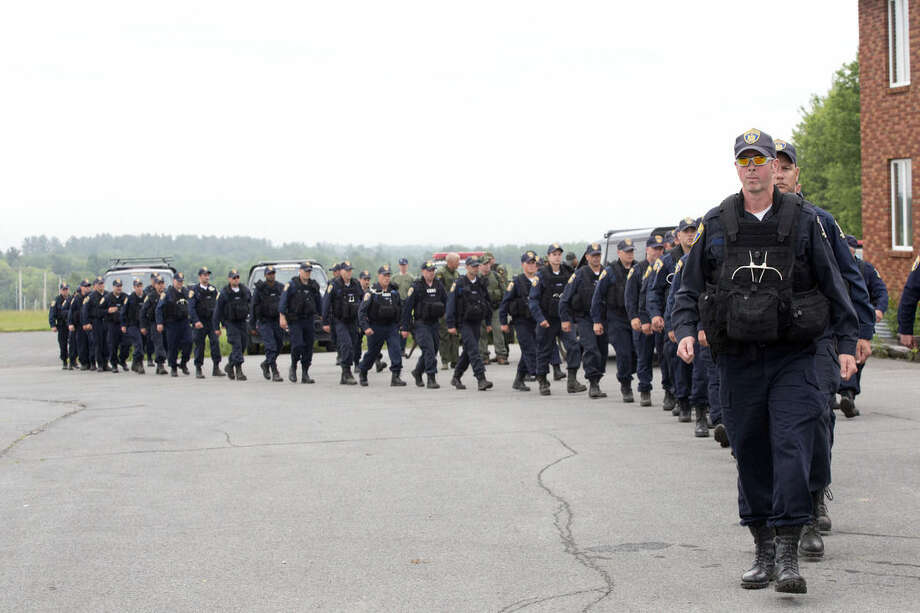 Dozens of corrections officers march off to the woods near the Clinton Correctional Facility, Tuesday, June 16, 2015 in Dannemora, N.Y. Search teams are back in the woods of northern New York looking for two convicted murderers who broke out of a maximum-security prison a week and a half ago. The more than 800 law enforcement officers searching for David Sweat and Richard Matt have steadily shifted their focus eastward along Route 374 leading from the village of Dannemora, home to Clinton Correctional Facility. (AP Photo/Mark Lennihan)