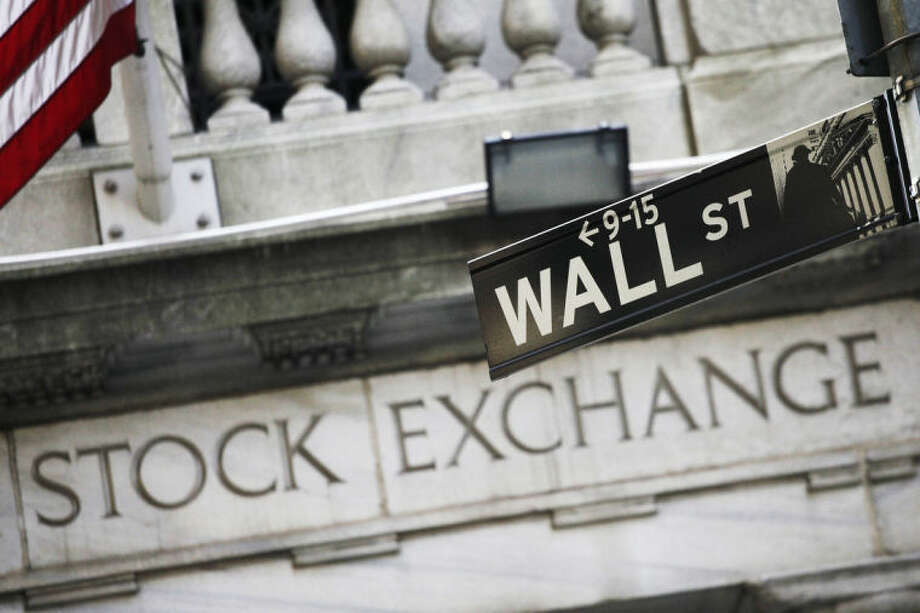 FILE - This July 16, 2013 file photo shows a Wall Street street sign outside the New York Stock Exchange in New York. Asian stock markets were mostly lower Monday, July 7, 2014, as investors looked ahead to U.S. corporate earnings following last week's strong job numbers. (AP Photo/Mark Lennihan, File)