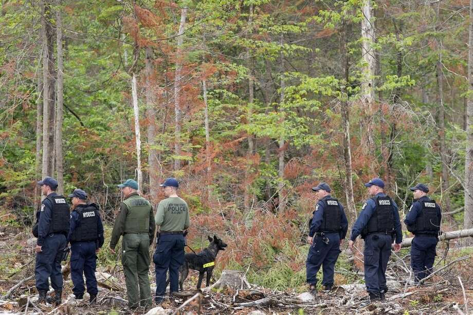 Corrections officers and a police dog start a search of woods near the Clinton Correctional Facility, Tuesday, June 16, 2015 in Dannemora, N.Y. Search teams are back in the woods of northern New York looking for two convicted murderers who broke out of a maximum-security prison a week and a half ago. The more than 800 law enforcement officers searching for David Sweat and Richard Matt have steadily shifted their focus eastward along Route 374 leading from the village of Dannemora, home to Clinton Correctional Facility. (AP Photo/Mark Lennihan)
