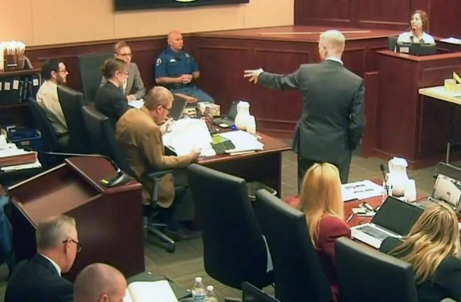 In this image taken from video, prosecutor George Brauchler, center right, gestures towards Colorado theater shooter James Holmes, top left in light-colored shirt and glasses, as Holmes' former psychiatrist Dr. Lynn Fenton, far right, testifies during his trial in Centennial, Colo., Tuesday, June 16, 2015. The psychiatrist who saw James Holmes repeatedly before he carried out his deadly attack on a Colorado movie theater said Tuesday that she had been warned before their first meeting that he said he was thinking of killing people. (Colorado Judicial Department via AP, Pool)