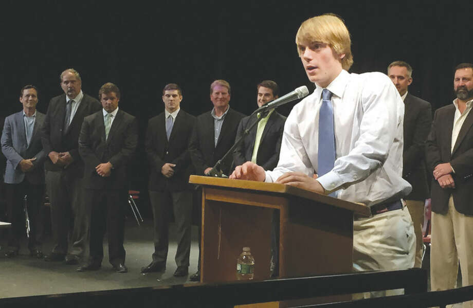 Hour photo/John NashWilton High senior student-athlete Christian Hansson gives his speech after becoming the 48th winner of the Lt. John G. Corr Award during the school's Senior Athletic Awards Night on Tuesday at Wilton High. Behind Hannson are the past winners of the award.