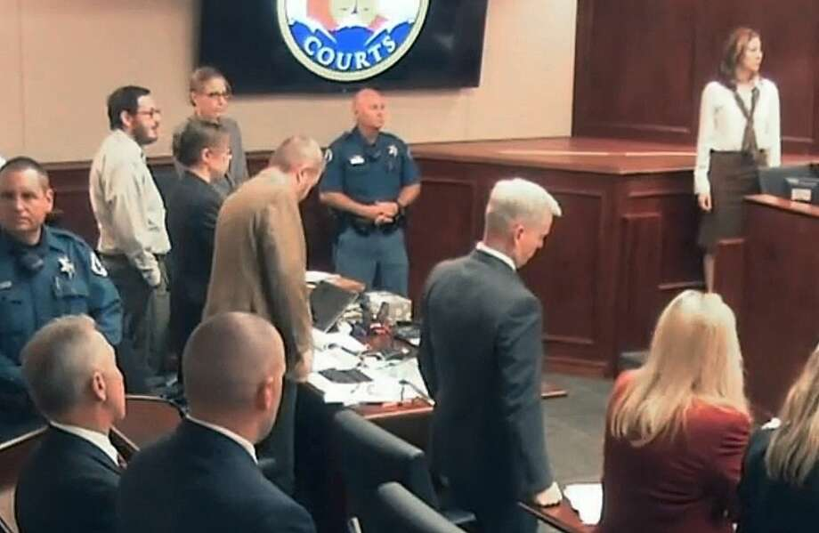 In this image taken from video, Colorado theater shooter James Holmes' former psychiatrist Dr. Lynne Fenton, far right top, prepares to testify in the Holmes trial, in Centennial, Colo., Tuesday, June 16, 2015. Holmes is pictured at top second from left in light-colored shirt and glasses. Dr. Fenton, who met with Holmes therapeutically before he carried out his deadly attack on a Colorado movie theater said Tuesday that she had been warned before their first meeting that he said he was thinking of killing people. (Colorado Judicial Department via AP, Pool)