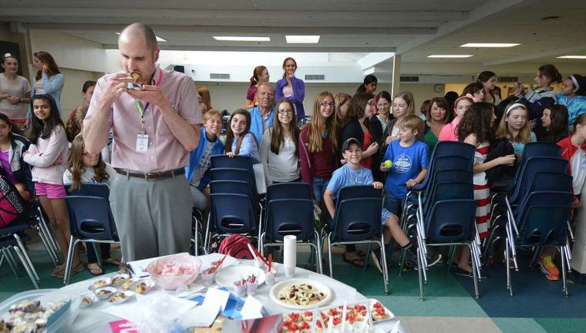 Teacher Andrew Nicsaji tries some appetizers from Switzerland as all eyes are on him during judging at the World Language Week food festival at Middlebrook School.