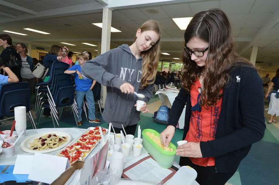 Students Meryl Kaduboski and Ellie Halgun serve up some fresh-made vanilla gelato for judges at the World Languages Week food festival at Middlebrook School.