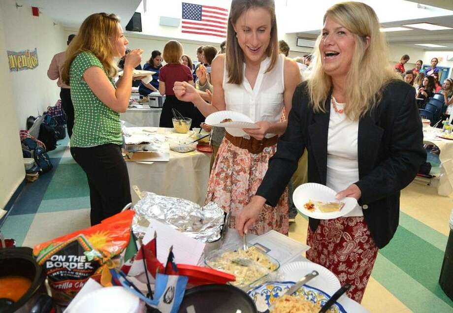 Teachers Joanna Cloherty and Jenifer Dunn sample a chicken marbella during the World Language Week food festival at Middlebrook School.