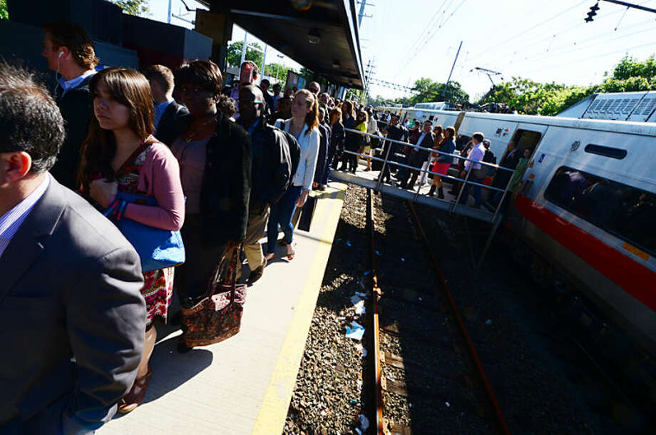 Hour photo / Erik Trautmann Passengers disembark a Eastbound Metro North train at East Norwalk after a 2 hour delay caused by a bridge failure at South Norwalk. Service was restored moments later.