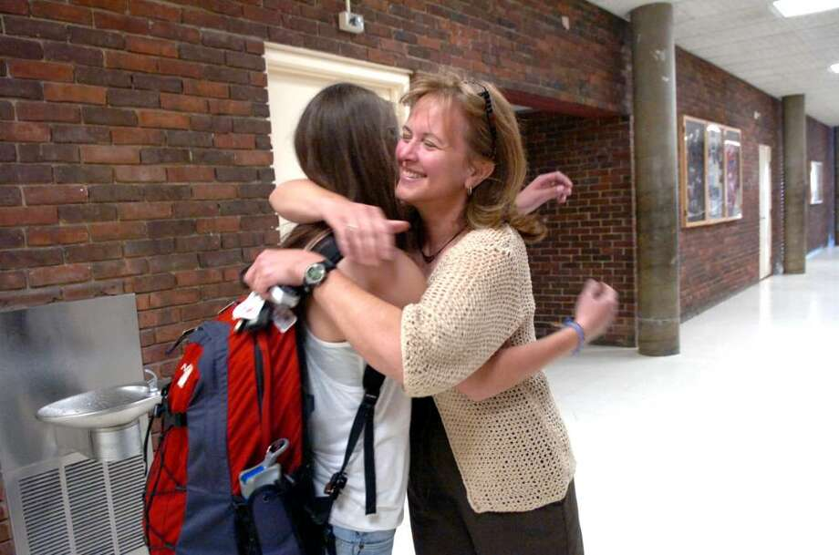 Greenwich High School band member Jessica Gorski, 15, returned from the band's trip to Greece and back at the school, gets a hug from Greece chaperone Colette Rogers on Thursday, April 22, 2010. Photo: Helen Neafsey / Greenwich Time