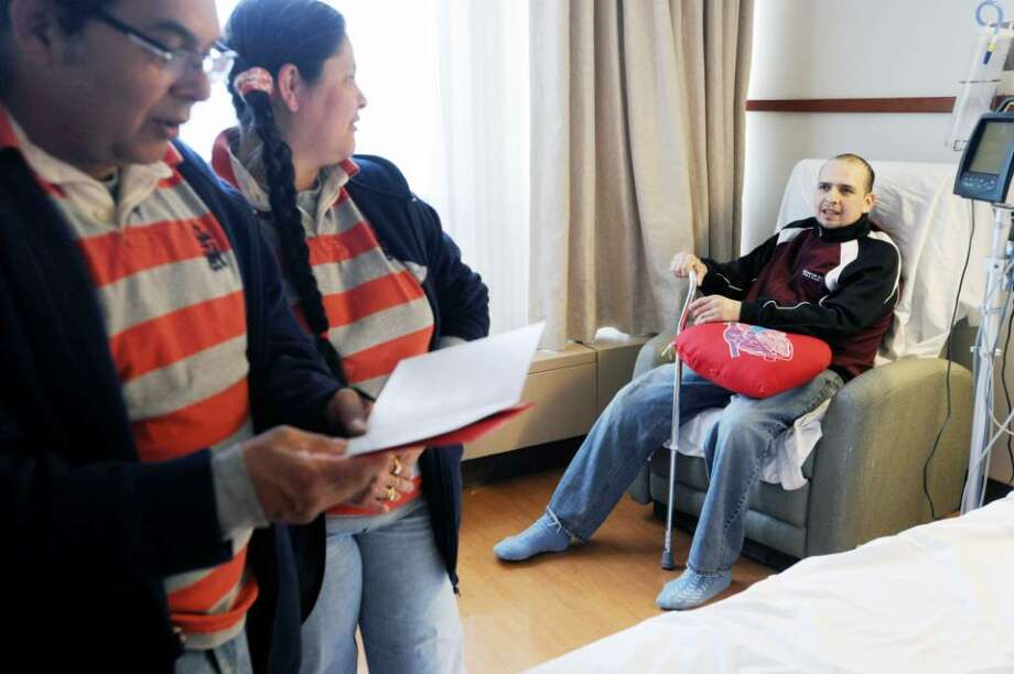 Dodamin Solis talks to his father Carlos Solis and his stepmother Norlba Solis moments before he was released from Stamford Hospital where doctors saved his life after he sustained a Stanford type a aortic dissection on the eve of his 30th birthday. Photo: Kathleen O'Rourke / Stamford Advocate