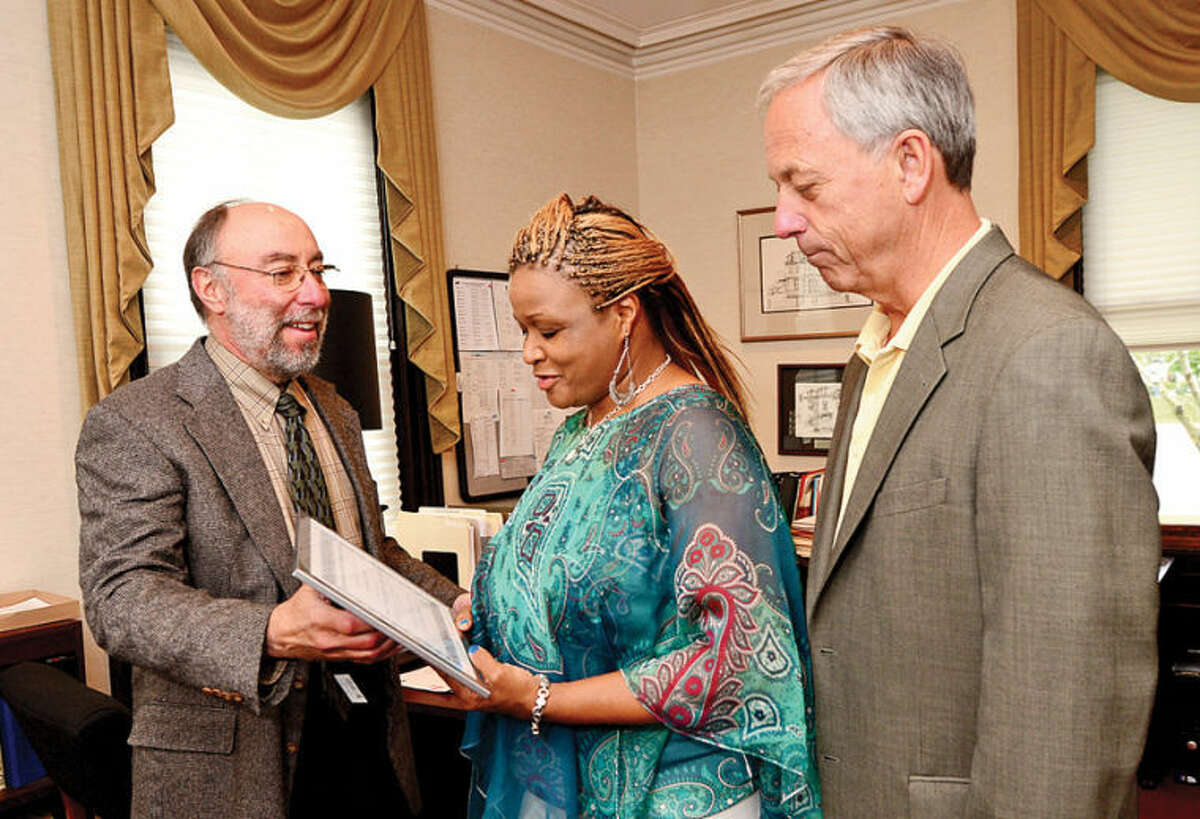 Hour photo / Erik Trautmann Child Guidance Center Executive Director Stuart Greenbaum and President of the Board of Trustees, Mark Lilliedahl, present Laverne Moore, center, with an certificate of appreciation for Moore's work in conceptualizing and writing a grant for the support group she founded, Parents Supporting Parents, for parents of children with behavioral problems.