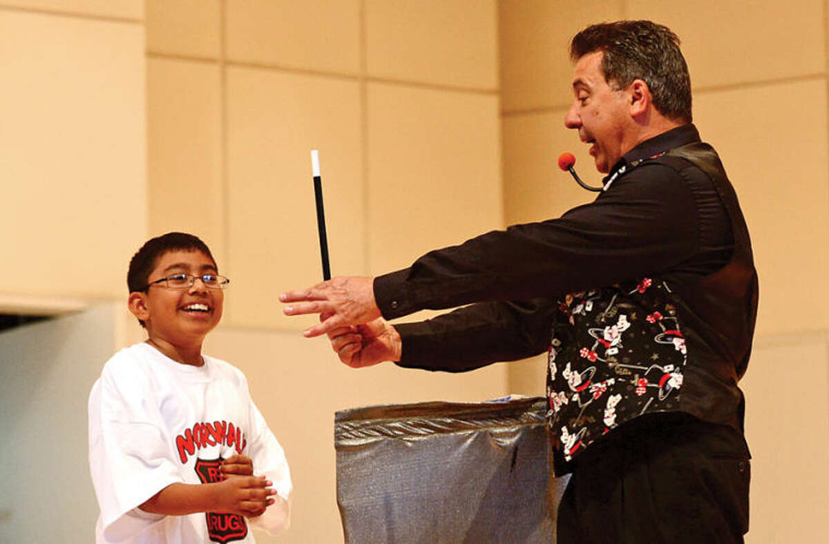 Hour photo / Erik Trautmann Naramake Elementary School 5th grader Jair Garcia performs a bit with magician Nick Moriello, aka Mr. Abracadabra, during The Norwalk Police Department DARE graduation for over a 1,000 Norwalk students Wednesday morning at City Hall.