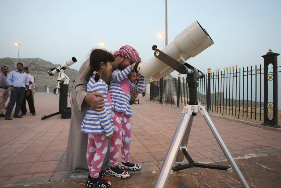 In this Tuesday, June 16, 2015 photo, a father holds his girls as one of them looks into a telescope during a moon sighting event on top of Jebel Hafeet mountain ahead of the holy month of Ramadan, in Al Ain, United Arab Emirates. The sighting of the new moon marks the beginning of Ramadan. (AP Photo/Kamran Jebreili)