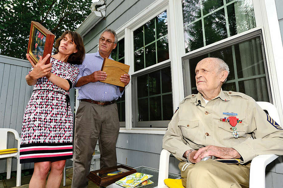 Hour photo / Erik Trautmann Honorary Consul of France for the State of Connecticut, Isabel Evelein, and Tom Loomis, look over the service medals of Robert Loomis, seated, after the elder Loomis was awarded the French Medal of Honor by Evelein during a ceremony at his home in Westport Wednesday. Loomis was born in Paris to an American father and during World War II, landed in Normandy as an American serviceman.