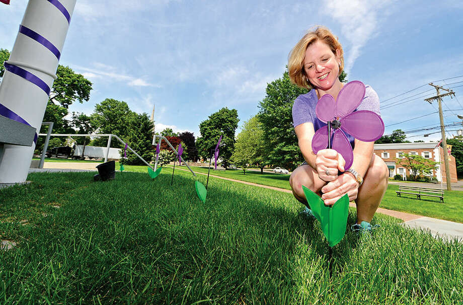 Hour photo / Erik Trautmann Leslie Hinshaw helps decorate the gazebo on the Norwalk Town Green in purple for the CT Chapter of the Alzheimer's Association to raise Alzheimer's awareness.