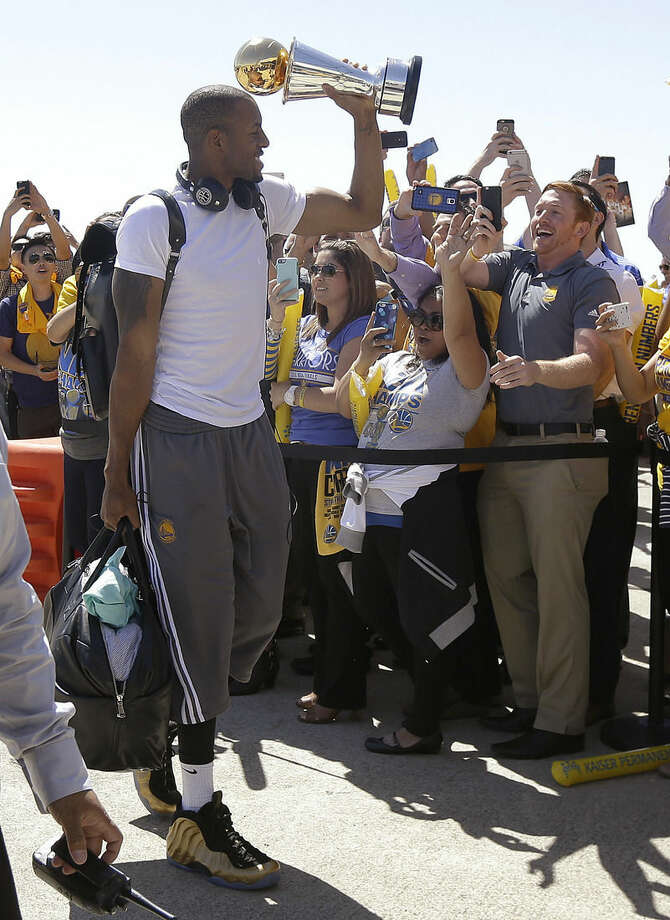 Golden State Warriors forward Andre Iguodala lifts the NBA Finals MVP trophy as he walks past team employees after the team's flight landed in Oakland, Calif., Wednesday, June 17, 2015. The Warriors defeated the Cleveland Cavaliers to win their first NBA championship since 1975. (AP Photo/Jeff Chiu)