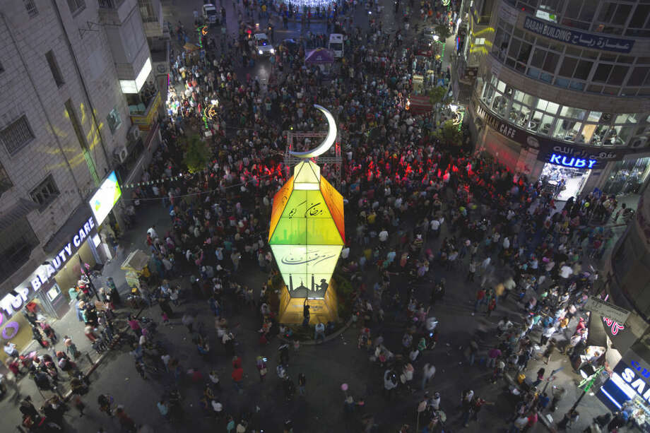 Palestinians watch the lighting of a big lantern to mark the upcoming Islamic holiday of Ramadan at the center of the West Bank city of Ramallah, Tuesday, June 16, 2015. (AP Photo/Majdi Mohammed)