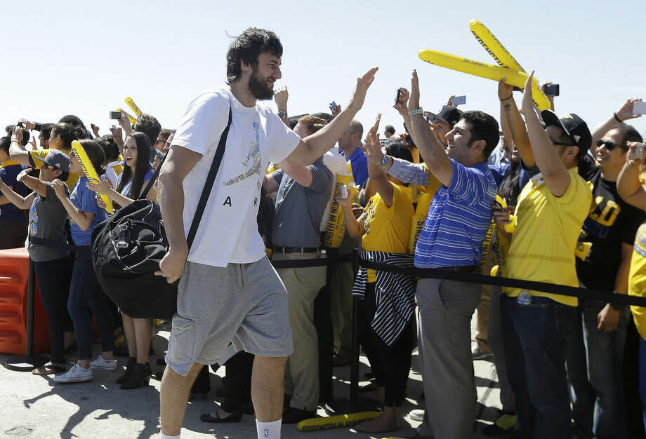 Golden State Warriors center Andrew Bogut greets team employees after the team's flight landed in Oakland, Calif., Wednesday, June 17, 2015. The Warriors defeated the Cleveland Cavaliers to win their first NBA championship since 1975. (AP Photo/Jeff Chiu)