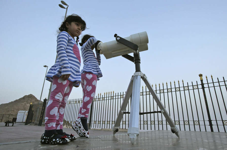 In this Tuesday, June 16, 2015 photo, girls look into a telescope during a moon sighting event on top of Jebel Hafeet mountain ahead of the holy month of Ramadan, in Al Ain, United Arab Emirates. The sighting of the new moon marks the beginning of Ramadan. (AP Photo/Kamran Jebreili)