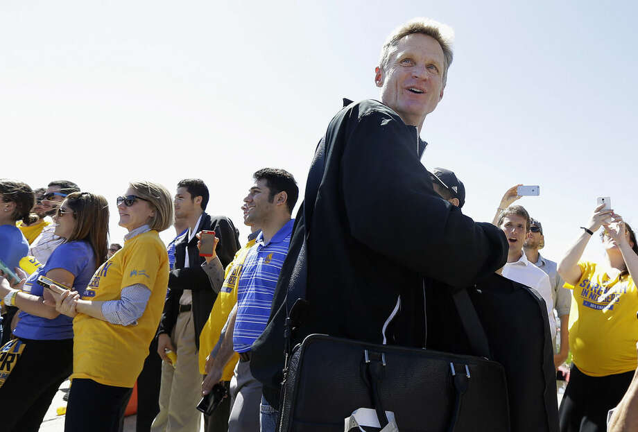 Golden State Warriors head coach Steve Kerr smiles as he walks past team employees after the team landed in Oakland, Calif., Wednesday, June 17, 2015. The Warriors beat the Cleveland Cavaliers to win their first NBA championship since 1975. (AP Photo/Jeff Chiu)