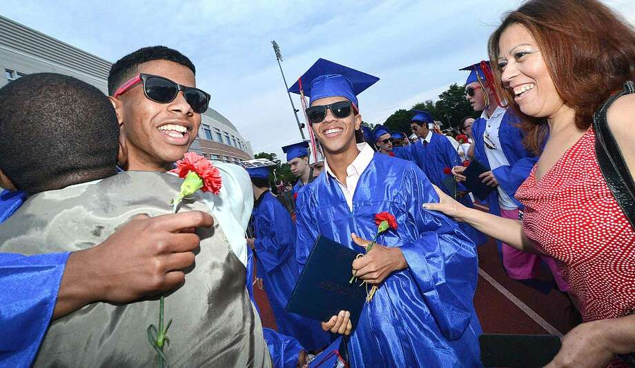 Hour Photo/Alex von Kleydorff Pierre Page and Loida Diaz greet Jose Peralto and Robert Diaz as they cross the 'M' and graduate from Brien McMahon High School