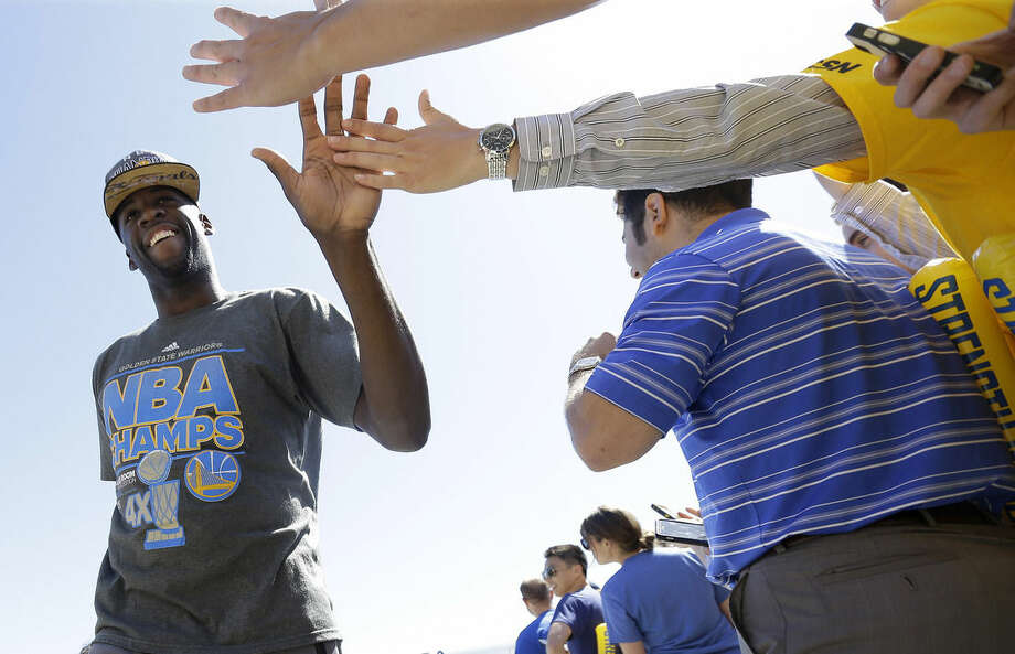Golden State Warriors forward Draymond Green, left, high fives team employees after the team landed in Oakland, Calif., Wednesday, June 17, 2015. The Warriors beat the Cleveland Cavaliers to win their first NBA championship since 1975. (AP Photo/Jeff Chiu)