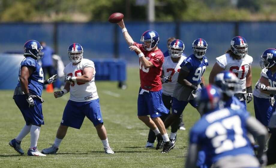New York Giants quarterback Eli Manning, center, throws a pass during an NFL football organized team activity, Thursday, May 29, 2014, in East Rutherford, N.J. (AP Photo/Julio Cortez)