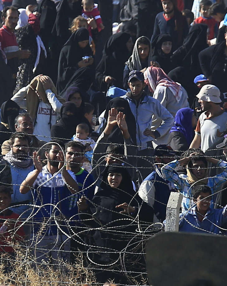 In this photo taken from the Turkish side of the border between Turkey and Syria, in Akcakale, Sanliurfa province, southeastern Turkey, Syrian refugees cheer and chant pro-Turkey slogans as they wait on the Syrian side of the border in order to cross, Sunday, June 14, 2015. The mass displacement of Syrians came as Kurdish fighters announced they are making headway toward the border town of Tal Abyad, a stronghold of the extremist group near the Turkish border. The loss of Tal Abyad would be a major blow to the Islamic State group as it is a major avenue for commerce for the extremist group.(AP Photo/Lefteris Pitarakis)