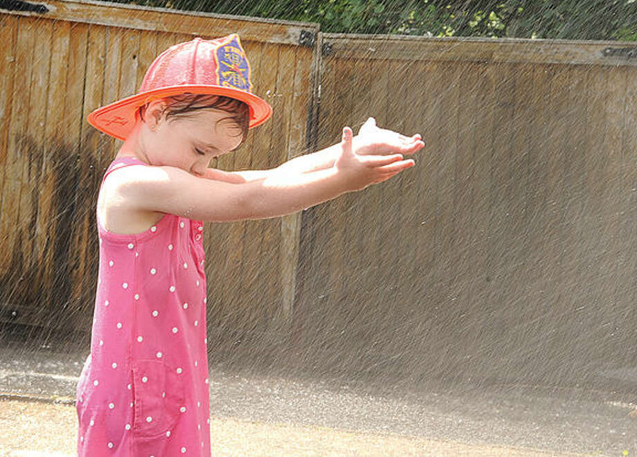 Emma Diamond 3, cools down in the sprinkler Sunday at the Georgetown Day celebration. Photo/Matthew Vinci