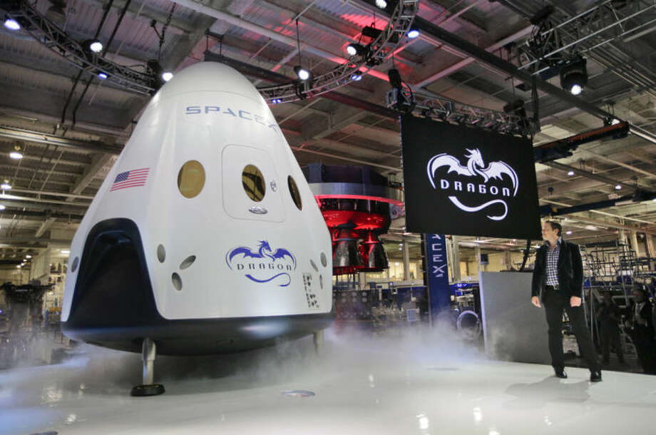 Elon Musk, right, unveils the SpaceX Dragon V2 spacecraft Thursday, May 29, 2014, in Hawthorne, Calif. SpaceX, which has flown unmanned cargo capsules to the International Space Station, unveiled the new spacecraft Thursday designed to ferry up to seven astronauts to the space station. (AP Photo/Jae C. Hong)